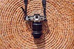 Oude uitstekende retro stijlcamera op de droge achtergrond van de de mat natuurlijke textuur van de waterhyacint stock afbeelding