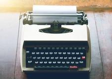 Oude uitstekende schrijfmachine met wit leeg document stock foto's
