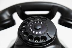 Oude uitstekende stationaire zwarte telefoon met wijzerplaat en een buis stock foto