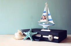 Oude Uitstekende sutcase met stuk speelgoed boat zeester en zeeschelp op houten raad reis en reisconcept retro gefiltreerd beeld Royalty-vrije Stock Afbeeldingen