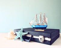 Oude Uitstekende sutcase met stuk speelgoed boat zeester en zeeschelp op houten raad reis en reisconcept retro gefiltreerd beeld Stock Foto