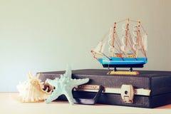 Oude Uitstekende sutcase met stuk speelgoed boat zeester en zeeschelp op houten raad reis en reisconcept retro gefiltreerd beeld Stock Fotografie