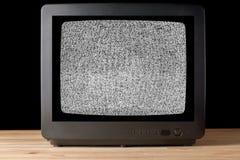 Oude uitstekende Televisietelevisor op houten lijst againt zwarte achtergrond zonder korrelig het lawaaieffect van de signaaltele stock afbeelding