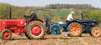 2 oude uitstekende tractor bij het ploegen van gelijke Royalty-vrije Stock Afbeelding