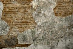 Oude uitstekende vuile bakstenen muur met schilpleister stock afbeelding