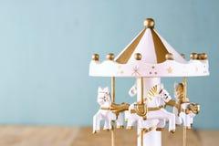 Oude uitstekende witte carrouselpaarden op houten lijst retro gefiltreerd beeld Stock Foto's