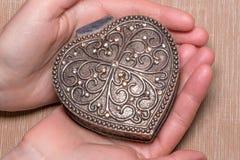 Oude uitstekende zilveren hart-vormige kist in vrouwelijke handen op licht gekleurde achtergrond Royalty-vrije Stock Fotografie