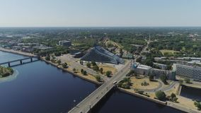 Oude van de de stads nieuwe bibliotheek van Riga slowmotion de hommelvlucht dichtbij brug met de luchtvlucht van het auto'sverkee stock videobeelden