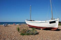 Oude varende die boot op een kiezelsteenstrand wordt getoond Stock Foto's