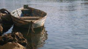 Oude vastgelegde boot in een rivier bij zonsondergang stock footage
