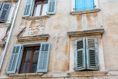 Oude vensters met blauwe blinden in het oude huis Uitstekende achtergrond Stock Foto's