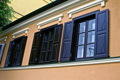 Oude vensters met houten blinden op de muur van het huis Stock Afbeeldingen