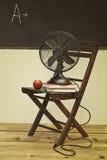 Oude ventilator met appel en boeken op stoel Stock Afbeeldingen