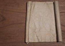 Oude verfrommelde document rol op houten lijst voor achtergrond stock foto