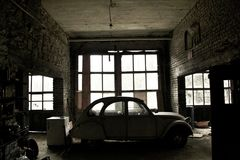Oude verlaten auto in een vergeten voor altijd verlaten garage Royalty-vrije Stock Afbeeldingen