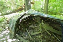 Oude verlaten auto in het bos stock afbeeldingen