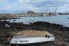 Oude verlaten boot op de pijler van het kustjacht bij de achtergrond Corralejo, Fuerteventura, Spanje stock foto's