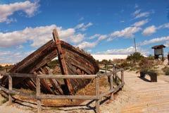 Oude verlaten boot op het strand stock fotografie