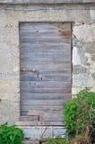 Oude, verlaten, grijze, houten deur bij de bouw stock afbeeldingen