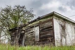 Oude verlaten loods op een grasrijk gebied Stock Foto
