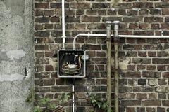 Oude verlaten muur met elektriciteitsmeter Royalty-vrije Stock Foto's