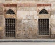 Oude verlaten muur met twee gesloten verfraaide houten vensters royalty-vrije stock foto's