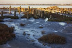 Oude verlaten pijlers van zoute extractie op estuar stock afbeelding
