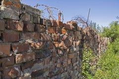 Oude vernietigde rode bakstenen muur met prikkeldraad Royalty-vrije Stock Afbeelding