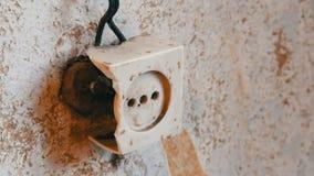 Oude vernietigde uitstekende contactdoos in muur van het huis stock video