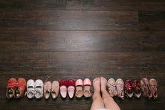 Oude versleten baby (kind, jong geitje) schoenen op de vloer babyvoeten (benen, Stock Fotografie