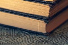 Oude versleten die boeken op geweven oppervlakte dichte omhooggaand worden gestapeld royalty-vrije stock afbeelding