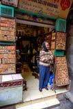Oude Vietnamese verkoopster in de deuropening van haar winkel Stock Foto's