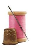 Oude vingerhoedje en naald met roze draad Royalty-vrije Stock Afbeeldingen
