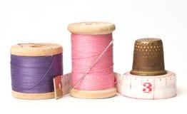 Oude vingerhoedje en naalden met draad Stock Fotografie