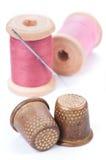 Oude vingerhoedjes en naald met roze draad Royalty-vrije Stock Afbeeldingen