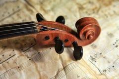 Oude viool op de achtergrond van nota's stock foto