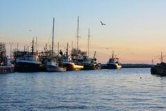 Oude visserijtreilers bij zonsondergang stock foto's