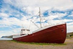 Oude vissersboot die op de fjordkust wordt doen mislukken, Westfjords, IJsland Stock Foto
