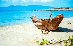 Oude vissersboot met anker op het strand Stock Afbeelding
