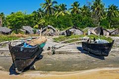 Oude vissersboot op het strand in tropisch met palmen, hutten en blauwe hemel Stock Fotografie
