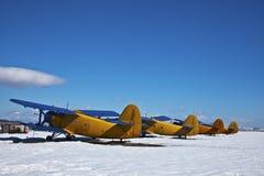 Oude vliegtuigen, die met sneeuw in een zonnige dag worden geparkeerd Royalty-vrije Stock Afbeeldingen