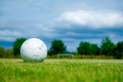 Oude voetbal op groen gras in Stadion Stock Afbeeldingen