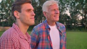Oude volwassen zoon koesteren en vader die, zich bevindt op tarwe of roggegebied, bos op achtergrond vooruit kijken stock footage