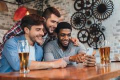 Oude vrienden die pret met smartphone hebben en bier drinken stock afbeeldingen