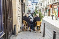 Oude vrienden in het praatje van koffiestoelen op baksteenstoep in Belleville, Stock Foto's