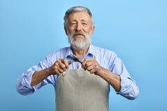 Oude vrolijke chef-kok of kelner in grijze schort, de blauwe vork van de overhemdsholding, lepel royalty-vrije stock fotografie