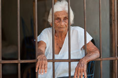Oude vrouw achter staven royalty-vrije stock fotografie