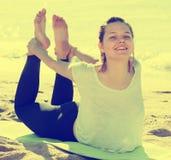 Oude vrouw 20-30 de jaar oefent yoga in witte T-shirt uit Royalty-vrije Stock Afbeelding