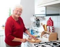 Oude vrouw in de keuken royalty-vrije stock afbeeldingen