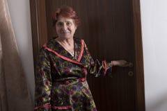 Oude vrouw dichtbij door een bruine houten deur royalty-vrije stock afbeeldingen